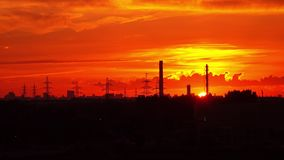 Industrial orange sunset. Sun goes down behind pipes and power pylons. Long shot Royalty Free Stock Photo
