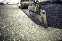 Industrial pavement truck laying fresh asphalt, bitumen during road works. Construction of highways. And road works stock images