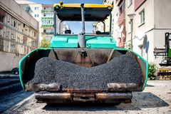 Industrial paver laying fresh asphalt and bitumen pavement Stock Image