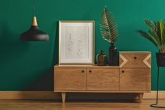 Stylish dark green interior. Industrial pendant light next to a stylish dresser and an art poster in a golden frame by a dark green wall of a modern bedroom Royalty Free Stock Photo