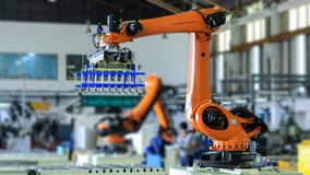 Industrial picking robot in production line manufacturer factory. Industrial robot is picking product and place into pallet for transfer to warehouse stock photography