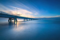 Industrial pier on the sea. Side view. Long exposure photography Stock Photos