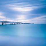 Industrial pier on the sea. Side view. Long exposure photography. Industrial pier on the sea horizon. Side view. Long exposure photography in a cloudy day Stock Photography