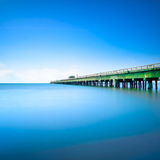 Industrial pier on the sea. Side view. Long exposure photography. Industrial pier on the sea horizon. Side view. Long exposure photography in a cloudy day Royalty Free Stock Photography