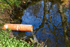 Industrial Pipe Dumping Waste Water. Into The river royalty free stock image