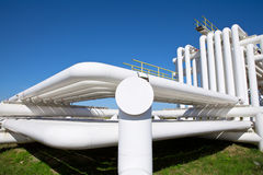 Industrial pipe with gas and oil and water. On a background of blue sky Royalty Free Stock Image