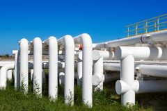 Industrial pipe with gas and oil and water. On a background of blue sky royalty free stock images