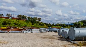 Industrial pipe storage lot under a sky filled with white puffy. Industrial pipe storage lot with various sizes and types of pipes under a sky filled with white Stock Photography