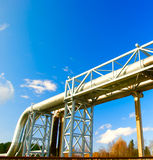 Industrial pipelines. On pipe-bridge against blue sky Stock Photo