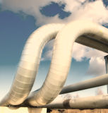 Industrial pipelines. On pipe-bridge against blue sky Stock Photos