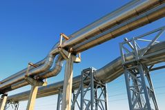 Industrial pipelines. On pipe-bridge against blue sky Royalty Free Stock Photography