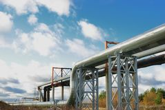 Industrial pipelines. On pipe-bridge against blue sky Royalty Free Stock Images