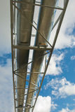 Industrial pipelines. On pipe-bridge against blue sky Stock Images