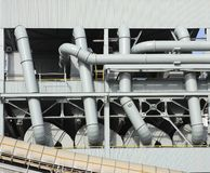 Industrial pipes and ducts. A view of a maze of industrial piping and ducts at a large mill or factory Stock Image