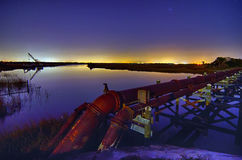 Industrial pipes and ocean harbor landscape at night Stock Images