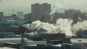 Industrial pipes pollute the atmosphere of the city with smoke in winter on a sunny day. Environmental pollution: pipe stock footage