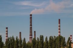 Industrial pipes and smoke. Heavy industry. Puffs from a high brick pipe against the background of the sky and foliage Stock Photo