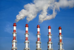 Industrial pipes with white smoke over blue sky. Horizontal photo Royalty Free Stock Photography