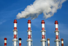 Industrial pipes with white smoke over blue sky. Horizontal photo Stock Images