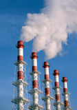 Industrial pipes with white smoke over blue sky, side view Stock Photography