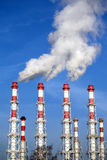 Industrial pipes with white smoke over blue sky. Vertical photo Royalty Free Stock Photo