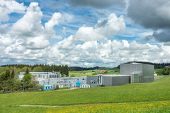 Industrial plant in a rural scenic landscape and flower meadow royalty free stock photo