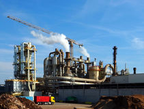 Industrial plant with smoke stacks and a crane stock images