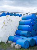 Industrial Plastic Barrels and Drums. A lot of plastic industrial blue and white barrels and drums in a pile Royalty Free Stock Photo