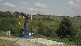Industrial platform with oil pumping units with rural scene in background  - stock footage