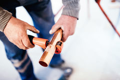 Industrial Plumber cutting a copper pipe with a pipe cutter. Stock Photography
