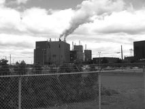 Industrial pollution 1. Industrial pollution chimney in urban city near St Lawrence river, Quebec, Canada - black and white picture grainy in purpose stock images