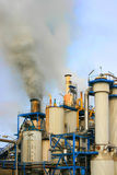 Industrial pollution. Smoke rising from industrial sugar refinery plant Royalty Free Stock Photo