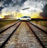 Industrial pollution. Twin railroad tracks with a large SUV speeding over and an airplane flying overhead.  Smoke stakes billowing smoke with an orange haze of Royalty Free Stock Images
