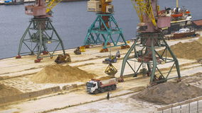 Industrial port area. Crane with bucket loads mortar sand in the truck. Shot at Sony camera in 4K stock footage