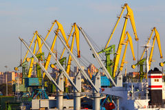 Industrial port cranes on unloadings of freights in port. Stock Photos