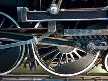 Industrial Power. Closeup view of the massive steel wheels of a vintage steam locomotive. You can see the gears, arms, wheels, counterweights and piping that stock photo