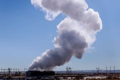 Industrial power plant, steaming cooling towers in blue sky. Industrial power plant station steaming cooling towers in blue sky electricity substation smoke royalty free stock image