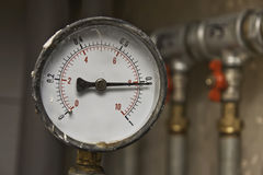 Industrial pressure meter and water pipes. Industrial pressure meter - barometer and water pipes in the background Royalty Free Stock Photos