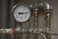 Industrial pressure meter and water pipes. Industrial pressure meter - barometer and water pipes in the background Stock Images