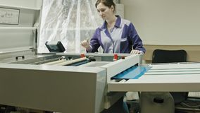 Industrial printing process - worker monitors the printing process stock video