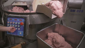 Industrial production of minced meat. Worker hands in gloves operating minced meat processing machine. stock video
