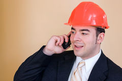 Industrial Professional. A man in a business suit and hard hat talks on his cell phone.  He could be a custom home builder or even an engineer or architect Royalty Free Stock Photos