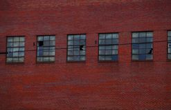 Industrial red brick facade with broken windows royalty free stock photography