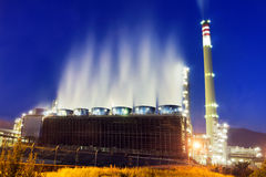 Industrial refinery at night with cooling water smoke Royalty Free Stock Photos