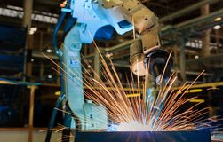 Industrial robot is welding assembly automotive part in car factory. Industrial robot is welding in automotive industrial factory royalty free stock image