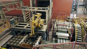 Industrial robotic arm works with bricks, putting them on a conveyor. stock video