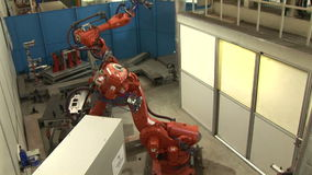 Industrial Robots on an Assembly Line. Images of two industrial robots assembling auto parts. Hydraulic operating robotic arms in a factory