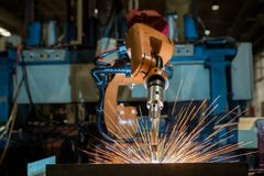 Industrial robots are welding assembly part in car factory. Industrial robots are welding automotive part in car factory stock photography