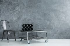 Industrial room with black chair. Designer vine shelf on industrial table on wheels in dark room with black chair, copy space interior concept royalty free stock image