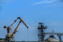 Industrial scene on sky background. Industrial scene with crane and river port facilities on blue sky background royalty free stock images